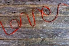 O amor da inscrição das lãs vermelhas rosqueia em um de madeira velho Fotografia de Stock Royalty Free