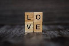 O amor da palavra, alinhado com blocos de madeira quadrados, em b de madeira escuro Foto de Stock Royalty Free