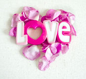 O amor da palavra e as pétalas cor-de-rosa no formulário do coração isolado no fundo branco de matéria têxtil Conceito do dia dos Imagem de Stock Royalty Free