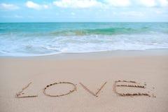 O amor da palavra da escrita da mão na praia pelo mar com ondas do branco e o céu azul Imagens de Stock Royalty Free