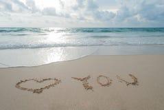 O amor da palavra você escrito na areia em uma praia no isla de Phuket Imagens de Stock