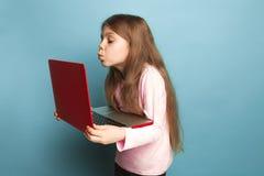 O amor do computador Menina adolescente com caderno em um fundo azul Expressões faciais e conceito das emoções dos povos fotos de stock royalty free
