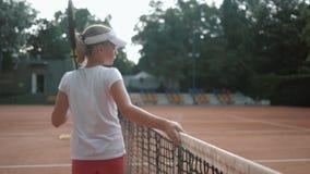 O amor do tênis, jogador de tênis da menina do adolescente dos esportes com raquete toca em líquido e anda ao longo da corte após vídeos de arquivo