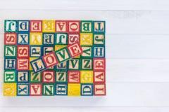 O AMOR escreve no bloco de madeira do alfabeto no fundo de madeira branco fotos de stock