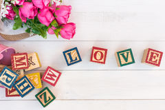 O AMOR escreve no bloco de madeira do alfabeto no fundo de madeira branco foto de stock