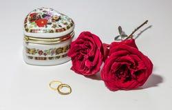 O amor romântico setup com as rosas vermelhas brilhantes com aneis de noivado do ouro e a caixa artística da joia no fundo claro Fotografia de Stock Royalty Free