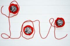 O amor vermelho da palavra com queques Imagem de Stock