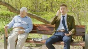 O anci?o ? livro de leitura no parque do th e o homem de neg?cios est? interrompendo-o com conversa??o alta filme