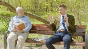 O anci?o ? livro de leitura no parque do th e o homem de neg?cios est? perturbando-o com conversa??o alta no telefone filme