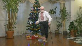O ancião agradável dança perto da árvore de Natal filme