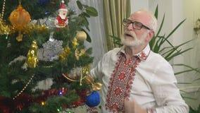 O ancião agradável ri perto da árvore de Natal vídeos de arquivo