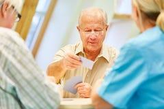 O ancião aposentado joga cartões imagens de stock royalty free