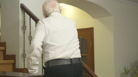 O ancião bonito anda acima das escadas em casa video estoque