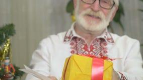 O ancião bonito está perto da árvore de Natal com presentes filme