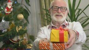 O ancião bonito nos vidros guarda presentes de Natal perto da árvore de Natal video estoque