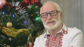 O ancião bonito ri perto da árvore de Natal filme