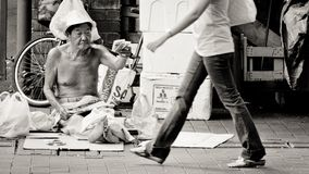 O ancião da pobreza vende blocos do lenço de papel na rua de Bugis, Singapura foto de stock