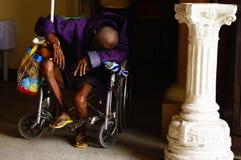 O ancião deficiente cai adormecido enquanto implorar quando em sua cadeira de rodas no portal da igreja fotografia de stock royalty free