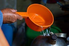 o ancião derrama a água da cubeta na chaleira, close-up fotografia de stock