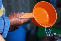 o ancião derrama a água da cubeta na chaleira, close-up fotos de stock royalty free