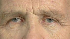 O ancião está abrindo seus olhos perto acima vídeos de arquivo