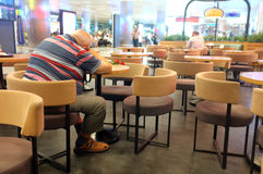 O ancião está dormindo na tabela fotografia de stock
