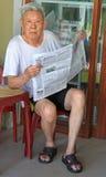 O ancião está lendo os jornais exteriores em Vinh, Vietname imagem de stock