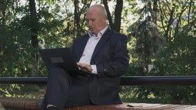 O ancião está sentando-se com o portátil em seus joelhos filme