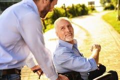 O ancião está sentando-se em uma cadeira de rodas no parque Atrás dele suportes seu filho O ancião olha felizmente em seu filho imagem de stock royalty free