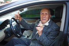 O ancião está sentando-se no carro, mantendo uma câmera e mostrar pequenos da ação os polegares-acima foto de stock