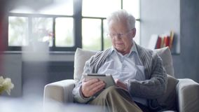 O ancião está usando o tablet pc em casa filme