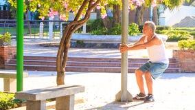 O ancião faz o up-down das ocupas dos exercícios da manhã em Polo no parque vídeos de arquivo