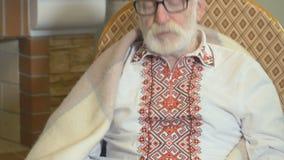 O ancião na roupa tradicional guarda papéis nas mãos e senta-se na cadeira de balanço video estoque