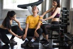 O ancião obtém a massagem por mulheres no gym da aptidão fotografia de stock