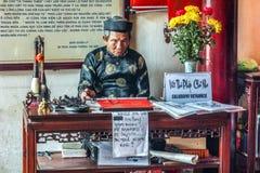 O ancião oferece a caligrafia no templo do filho de Ngoc, Hanoi. Imagem de Stock Royalty Free