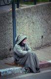O ancião pobre do mendigo senta-se na rua da cidade com o vestido tradicional de musselina, Marrocos fotografia de stock royalty free