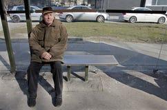 Sénior na estação de autocarro Imagem de Stock