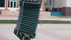 O andarilho anda em torno da cidade e leva um acordeão Amarrado por cordas Close-up vídeos de arquivo