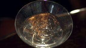 O anel de ouro cai em um vidro de Martini filme