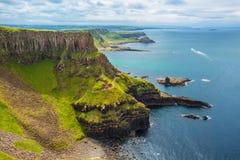 O anfiteatro, a baía de Reostan do porto e a calçada gigante do ` s no fundo, condado Antrim, Irlanda do Norte, Reino Unido Foto de Stock