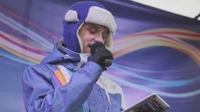 O anfitrião do homem novo no revestimento roxo, chapéu morno com microfone leu o texto na fase concert video estoque