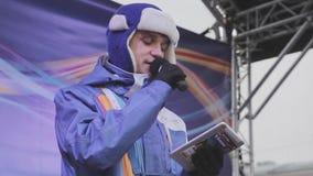 O anfitrião do homem novo no revestimento roxo, chapéu morno com microfone leu o texto na tabuleta na fase concert filme