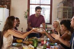 O anfitrião e os amigos passam o alimento em volta da tabela em um partido de jantar Imagens de Stock