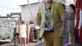 O animador no traje do palhaço faz a bolha de sabão grande no terraço do restaurante Miúdos video estoque
