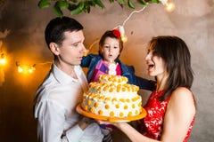 O aniversário das crianças do feriado da família do tema e o sopro para fora de velas no grande bolo família nova de três povos q imagem de stock royalty free