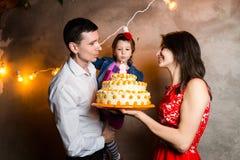 O aniversário das crianças do feriado da família do tema e o sopro para fora de velas no grande bolo família nova de três povos q Fotografia de Stock Royalty Free