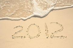 O ano 2012 escrito na areia na praia Imagens de Stock Royalty Free