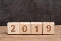 O ano 2019 começa bu de madeira do bloco do conceito, o simples e o mínimo do cubo fotografia de stock