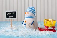 O ano novo 2017 é conceito de vinda Boneco de neve com o suporte vermelho do trenó escrito próximo no sinal de sentido Fotografia de Stock Royalty Free