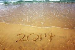 O ano novo 2014 é conceito de vinda escrito na areia da praia Fotos de Stock Royalty Free